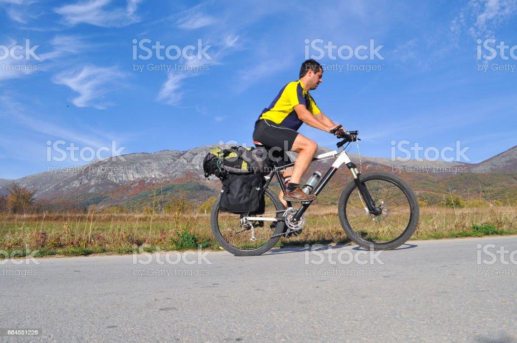 Viajero monta una bicicleta en camino bajo una montaña - foto de stock