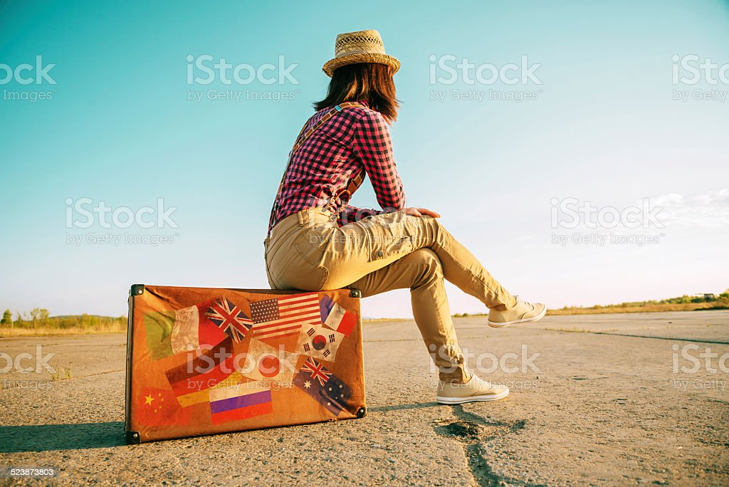 Traveler sits on suitcase with stamps flags stock photo