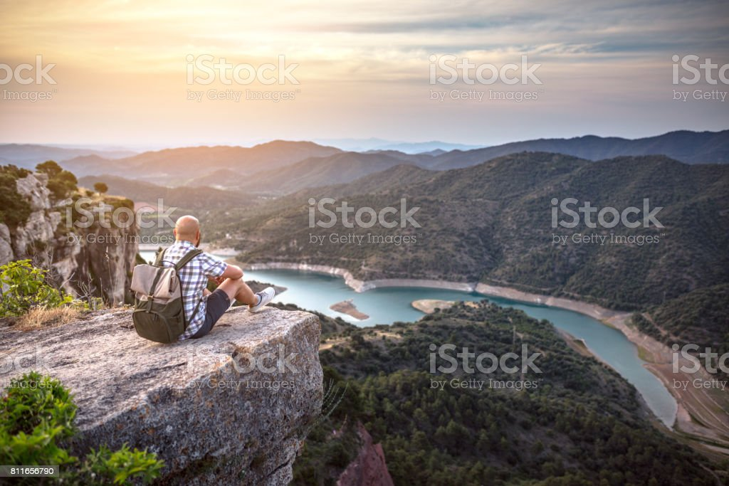 Traveler sits on the edge of a rock and enjoys the view of river in mountains stock photo