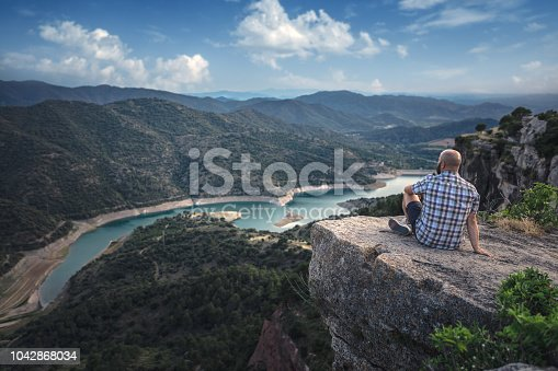 Traveler sitting at the edge of the mountain, beautiful valley in front of him
