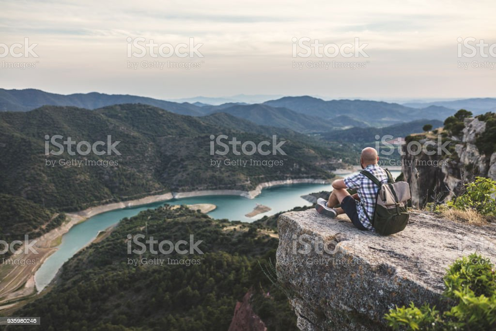 Traveler sitting at the edge of the mountain, beautiful valley in front of him stock photo