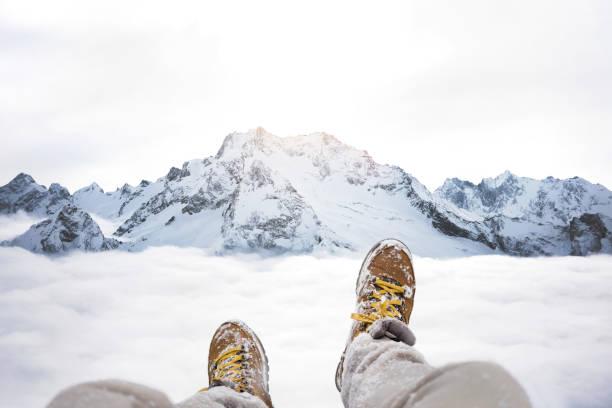 Reisende auf Berggipfel, POV Blick auf große Winterberge oberhalb der Wolke sitzen und Wanderschuhe. Beine von Close Up auf Hintergrund der schneebedeckten Felslandschaft – Foto