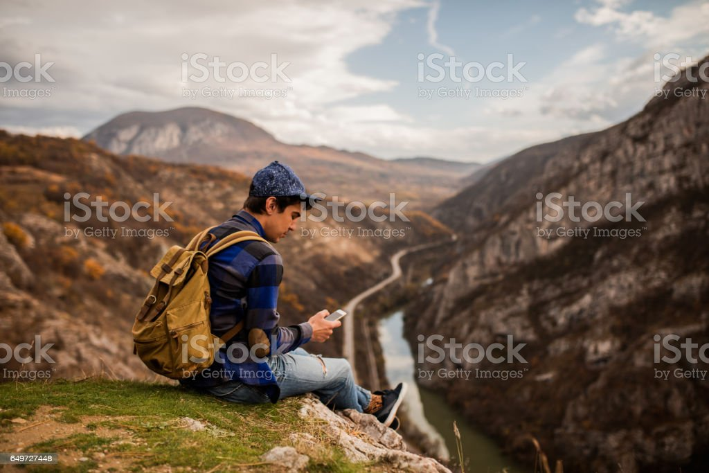 Traveler sitting on mountain top reading messages stock photo