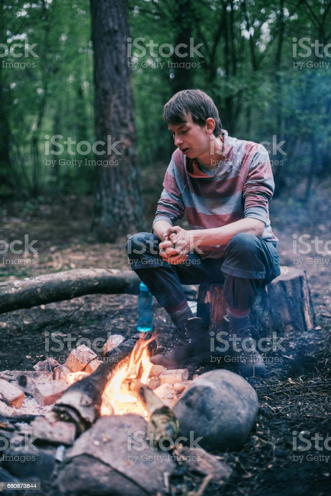 Traveler sitting on tree stump at campfire enjoying the warmth. royalty-free stock photo