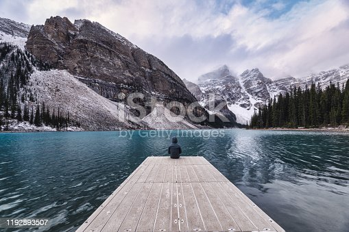 Traveler sitting on wooden pier with rocky mountain in Moraine lake at Banff national park, Canada