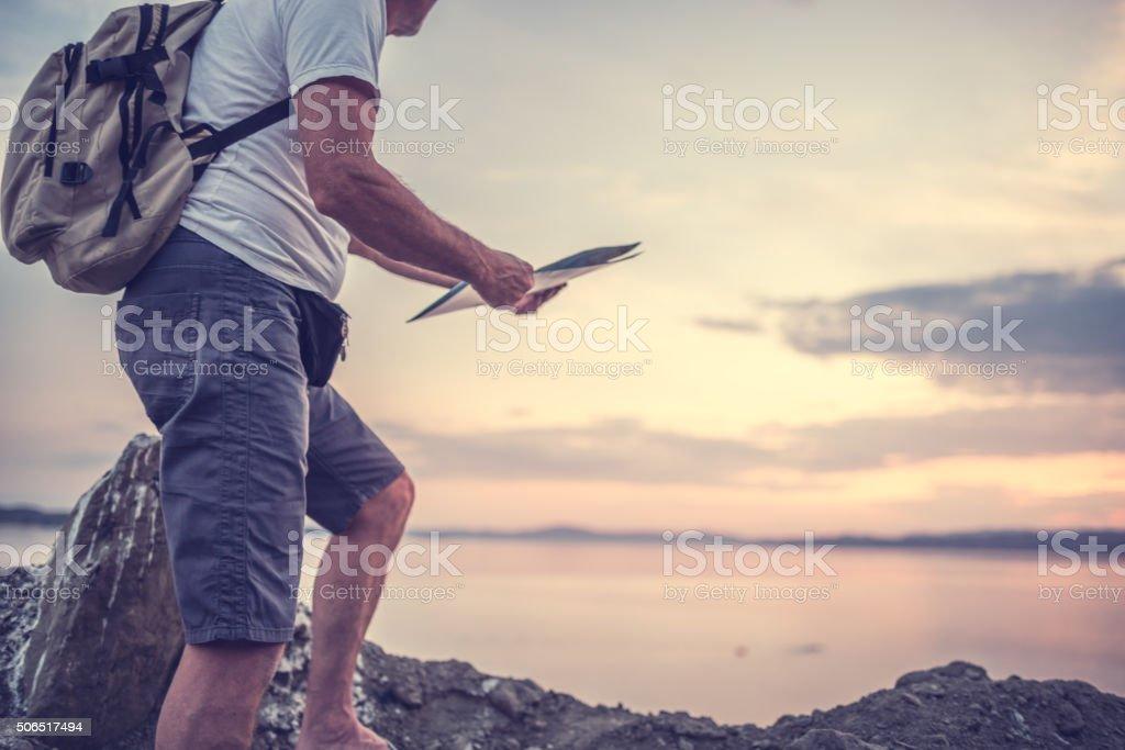 Traveler standing on the rocks near the sea stock photo