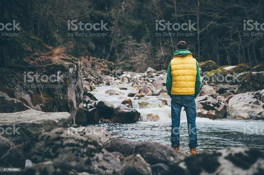 Traveler stands near the river in mountains and looking ahead stock photo