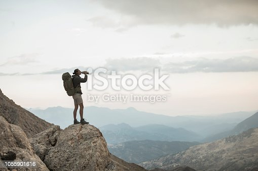 Young man standing on the cliff drinking water.