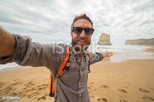Young man takes a selfie portrait on Gibsons steps beach in Twelve Apostles Marine National Park, Great Ocean Road, Victoria, Australia.