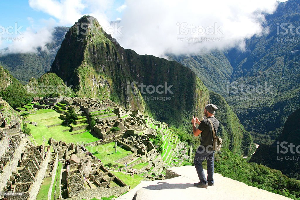Traveler taking picture with cell phone in Machu Picchu, Peru stock photo
