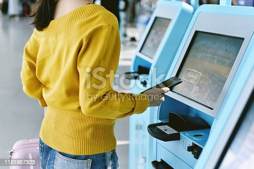 Traveler using a self check-in machine kiosk service at airport, Technology and smart application to confirm flight booking details, Travel conce