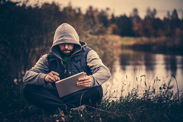 Traveler using digital tablet sitting in the forest near lake stock photo
