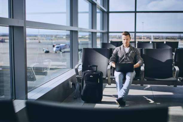 traveler using laptop in airport terminal - sala d'imbarco foto e immagini stock