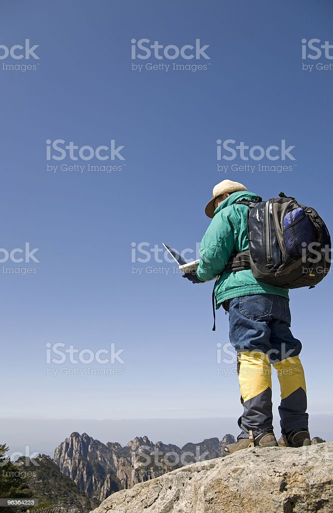 Traveler using laptop on hiking trip royalty-free stock photo