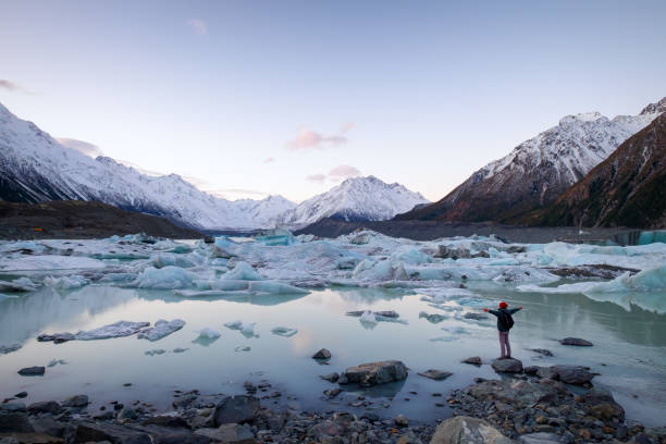 Traveler viewing icebergs landscape and snow mountains in New Zealand stock photo