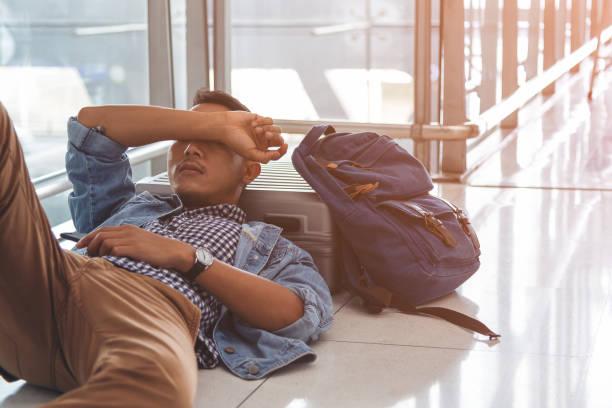 Voyageur attendant à la zone de départ de l'aéroport pour son vol de retard.  Jeune voyageur dormant sur le plancher avec ses bagages, des choses sur le sol d'aéroport. Jeune voyageur fatigué font une sieste sur la zone de terminal d'aéroport. - Photo