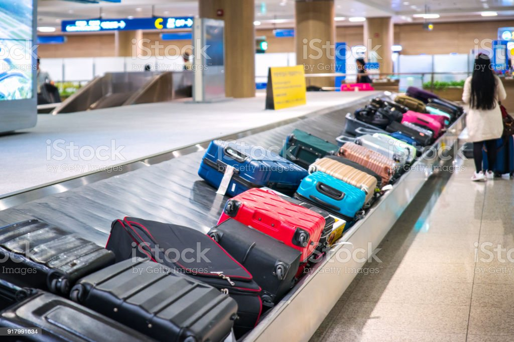 Traveler waiting for a travel bag on the belt in airport stock photo