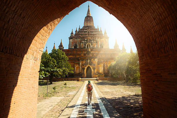 traveler walking along road to htilominlo temple in bagan. burma - voyages en asie photos et images de collection