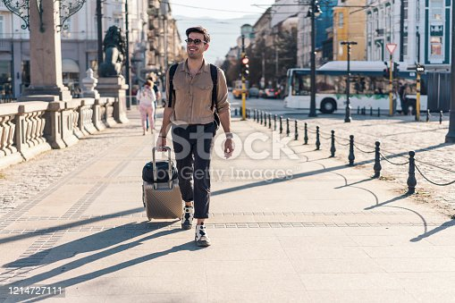 Cheerful young man walking on the street, pulling his suitcase