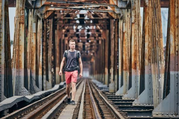Traveler walking on railway bridge Young man with backpack walking on railway bridge. Themes adventure, hiking and travel. railway bridge stock pictures, royalty-free photos & images