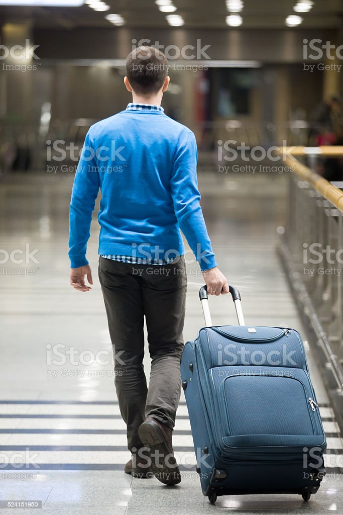 Traveler walking with suitcase at airport stock photo