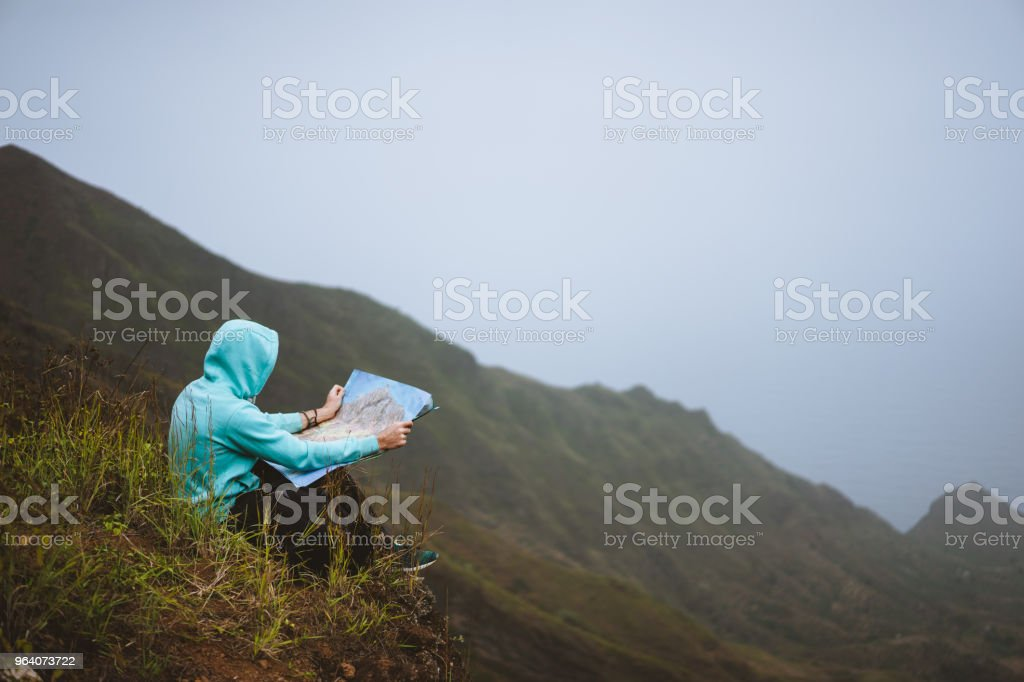 Traveler wear blue hoodie with the map sitting on the hill of a mountain in front of a gorgeous panorama view t othe valley - Royalty-free Achievement Stock Photo
