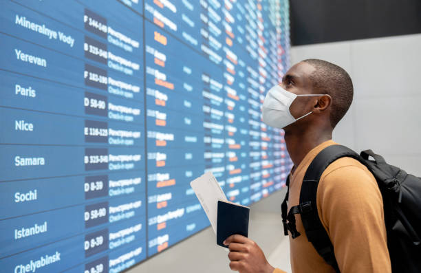 traveler wearing a facemask at the airport and looking at the flight schedule - covid flight imagens e fotografias de stock