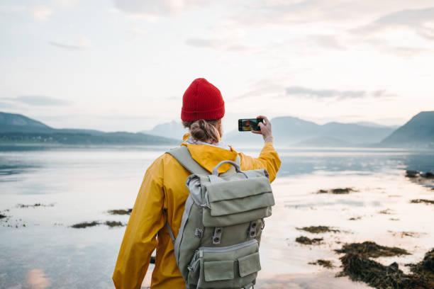Reisende tragen gelben Regenmantel fotografieren per Smartphone fantastische Nordlandschaft während der Reise Skandinavien. Mann Tourist macht ein Foto große Berg Natur – Foto