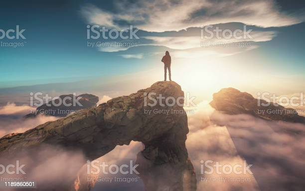 Photo of Traveler with a backpack standing on a mountain peak above clouds. 3d render illustration