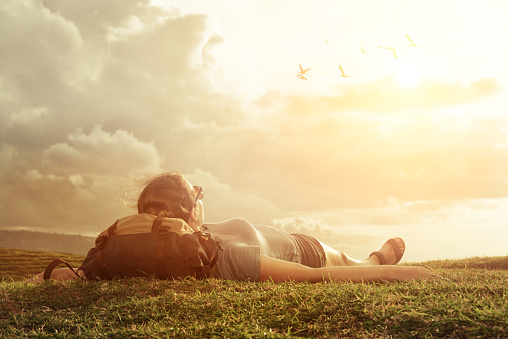 Carefree happy woman traveler with backpack lying on green grass on top of mountain edge cliff enjoying sun and clouds.