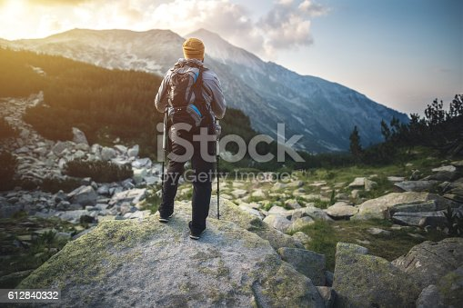istock Traveler with backpack looks on a mountain peak on sunset 612840332