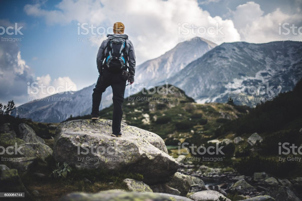 Traveler with backpack looks on a mountain peak – Foto