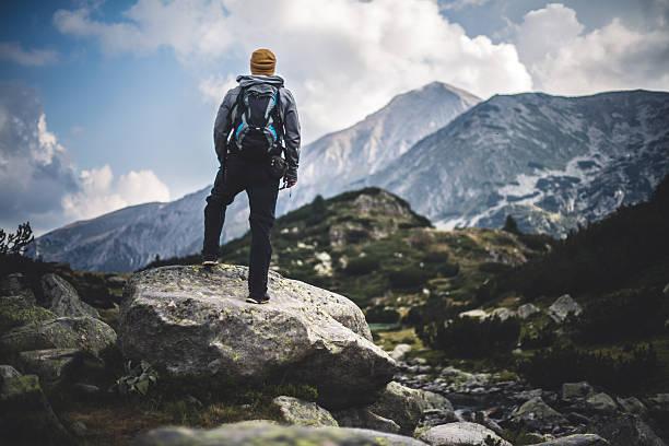 traveler with backpack looks on a mountain peak - mochilero fotografías e imágenes de stock