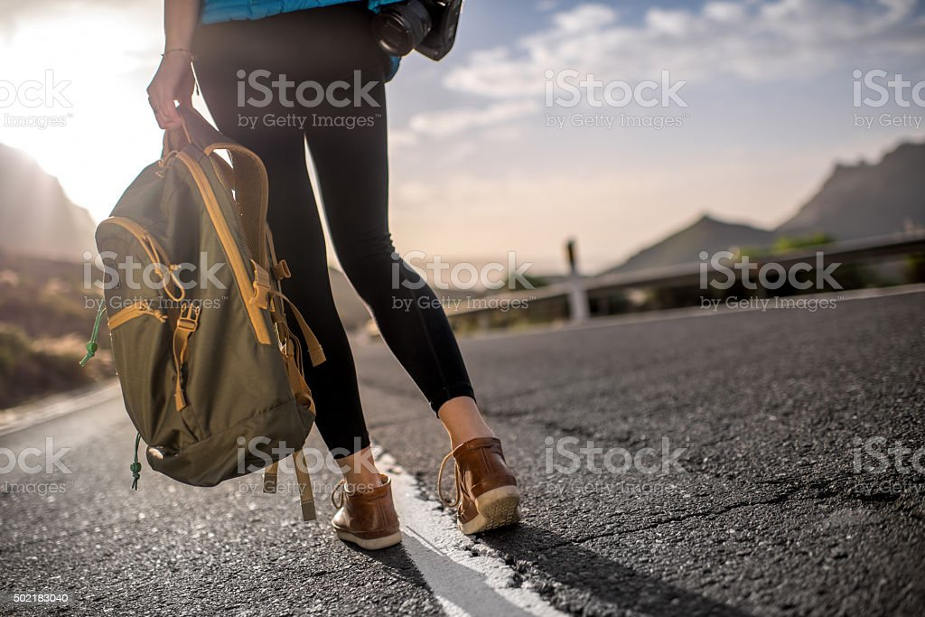 Traveler with backpack on the road stock photo