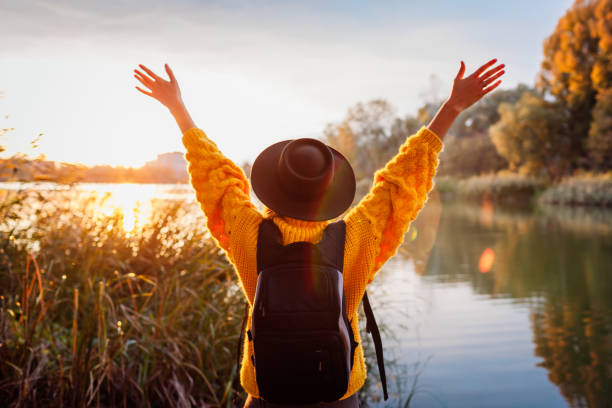 Traveler with backpack relaxing by autumn river at sunset. Young woman raised arms feeling free and happy