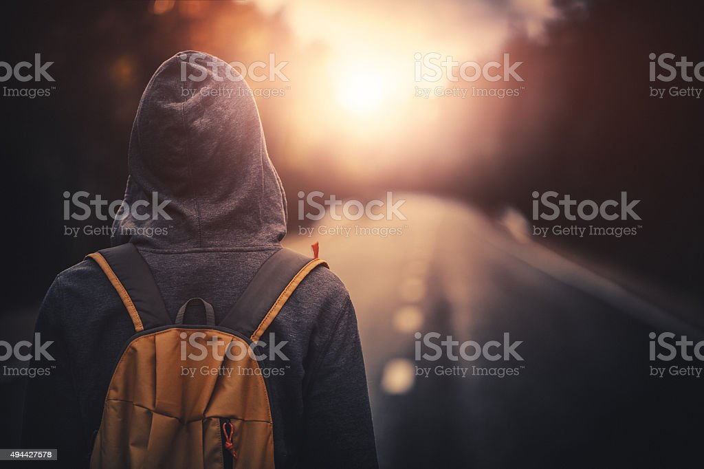Traveler with backpack walking forward alone at sunset stock photo