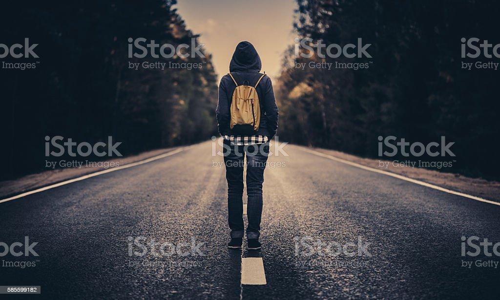 Traveler with backpack walking forward alone stock photo
