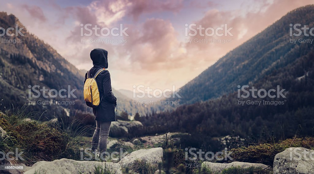 Traveler with backpack walking in mountains in the evening stock photo