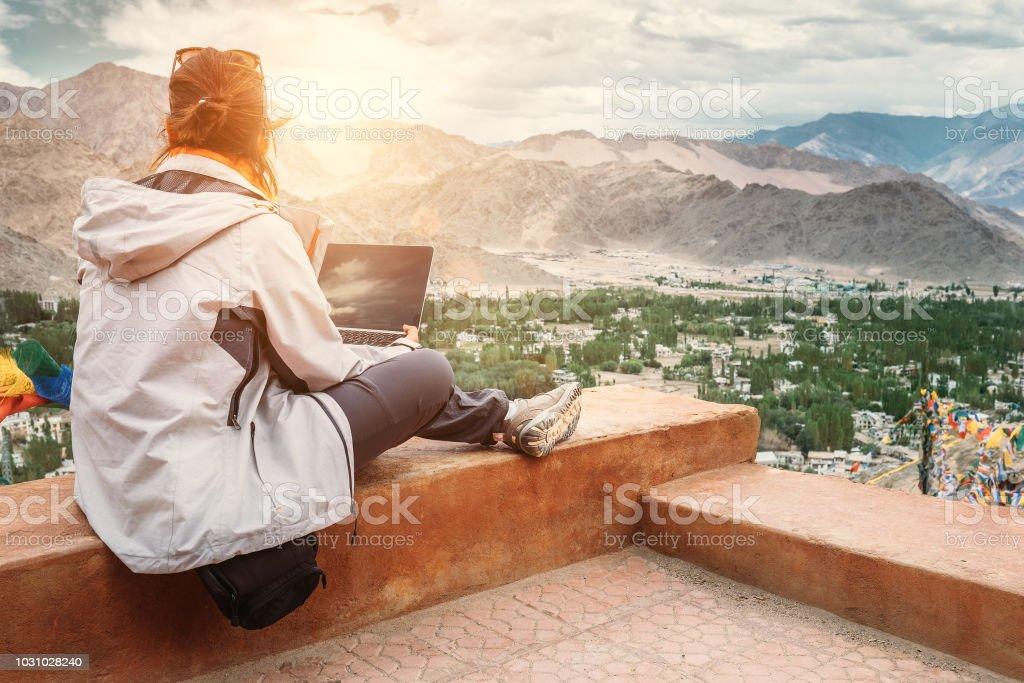 Reisende mit Laptop sitzt am oberen Aussichtspunkt auf dem Bergtal – Foto