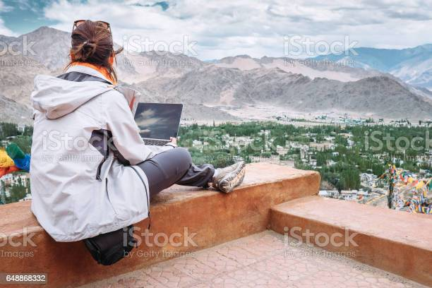 Traveler with laptop sits on top view point on the mountain valley picture id648868332?b=1&k=6&m=648868332&s=612x612&h=u4ww orvpnimsxcc8pnxart5 eiwlaipwrpmwevjj9a=