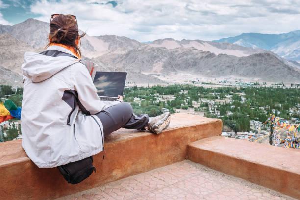 traveler with laptop sits on top view point on the mountain valley - reiseblogger stock-fotos und bilder