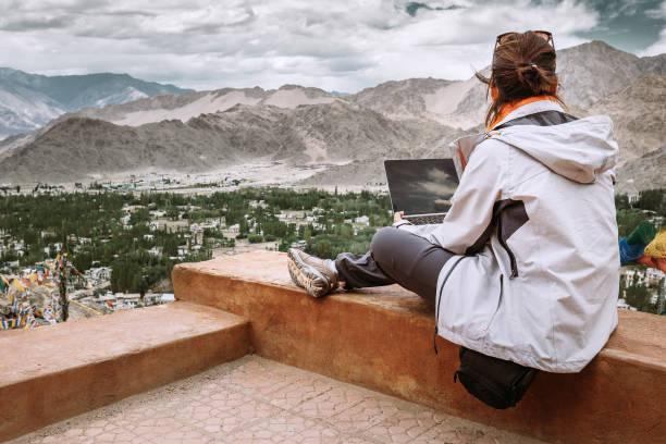 reisende mit laptop sitzt am oberen aussichtspunkt auf dem bergtal - reiseblogger stock-fotos und bilder