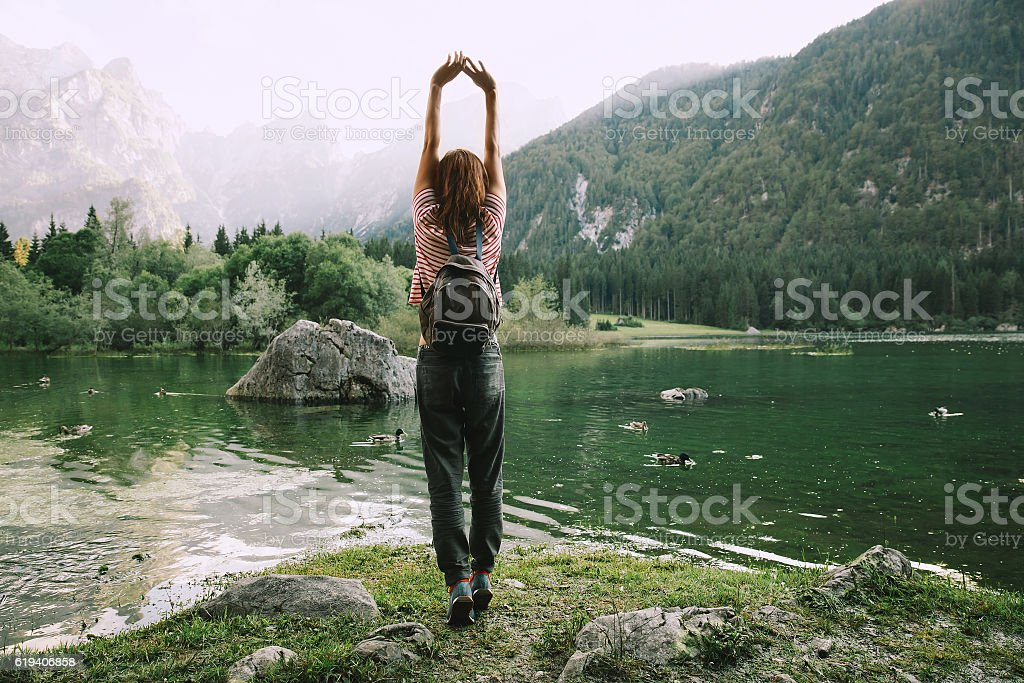 Traveler with raised arms up on the nature stock photo