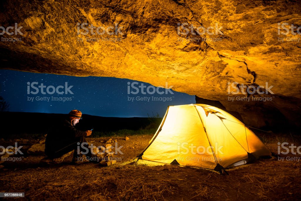 Viajante com smartphone perto da barraca de acampamento brilhante na gruta à noite sob um céu estrelado - foto de acervo