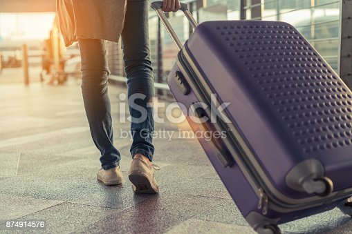 istock Traveler with suitcase in airport concept.Young girl  walking with carrying luggage and passenger for tour travel booking ticket flight at international vacation time in holiday rest and relaxation. 874914576