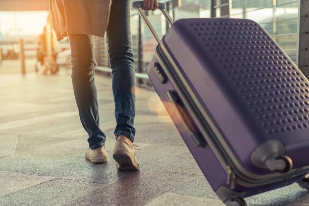 概念の空港でスーツケースを持っての旅行者。休日の休息とリラクゼーションの国際休暇時に荷物とツアー旅行予約航空券のフライトの乗客を運ぶと歩いている若い少女。 - 空港 ストックフォトと画像