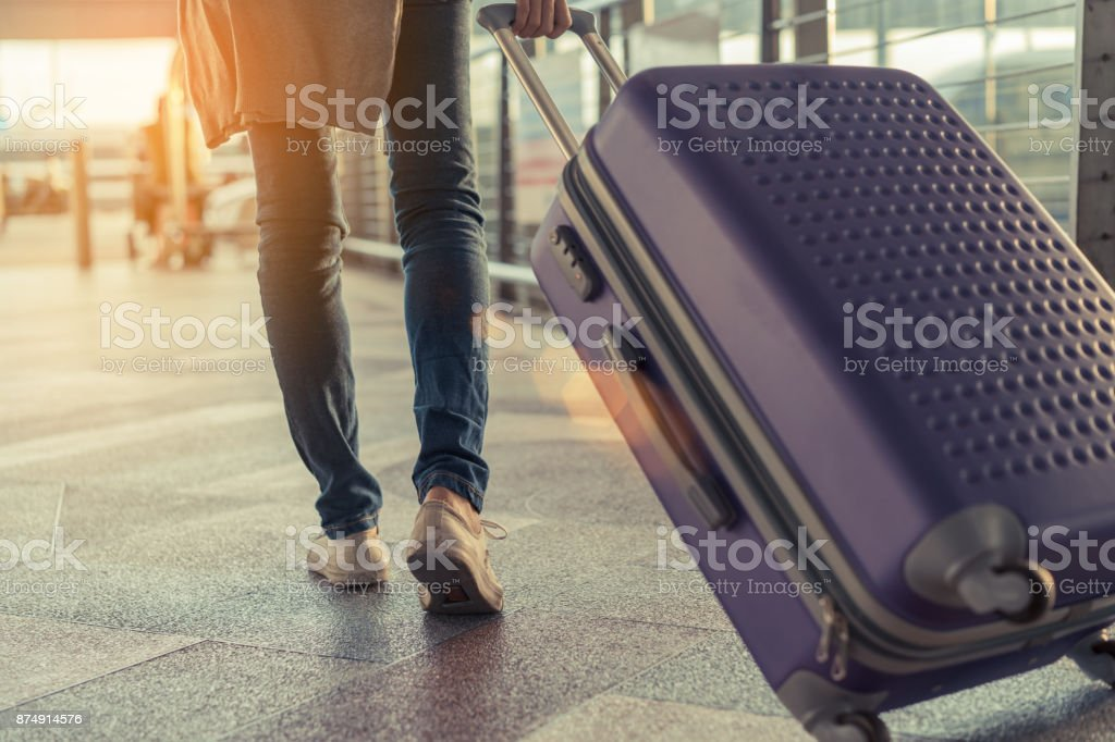 Traveler with suitcase in airport concept.Young girl  walking with carrying luggage and passenger for tour travel booking ticket flight at international vacation time in holiday rest and relaxation. stock photo