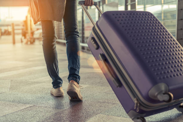 traveler with suitcase in airport concept.young girl  walking with carrying luggage and passenger for tour travel booking ticket flight at international vacation time in holiday rest and relaxation. - airport stock photos and pictures