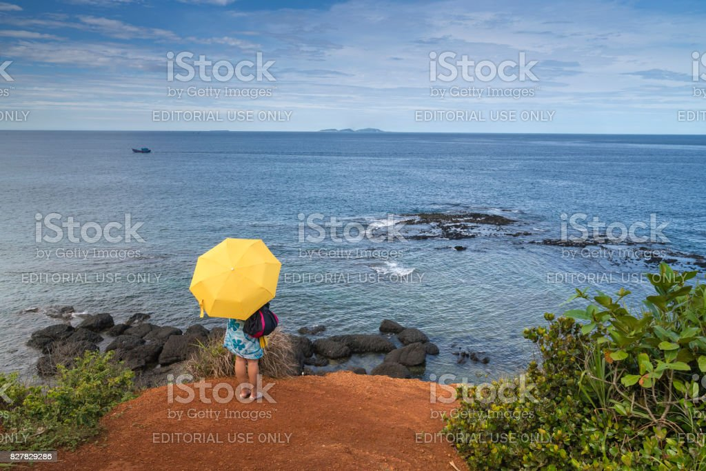 traveler with yellow umbrella is standing on the coast stock photo