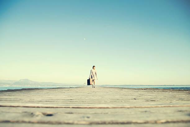 viaggiatore donna cammina a destinazione con la valigia - donna valigia solitudine foto e immagini stock